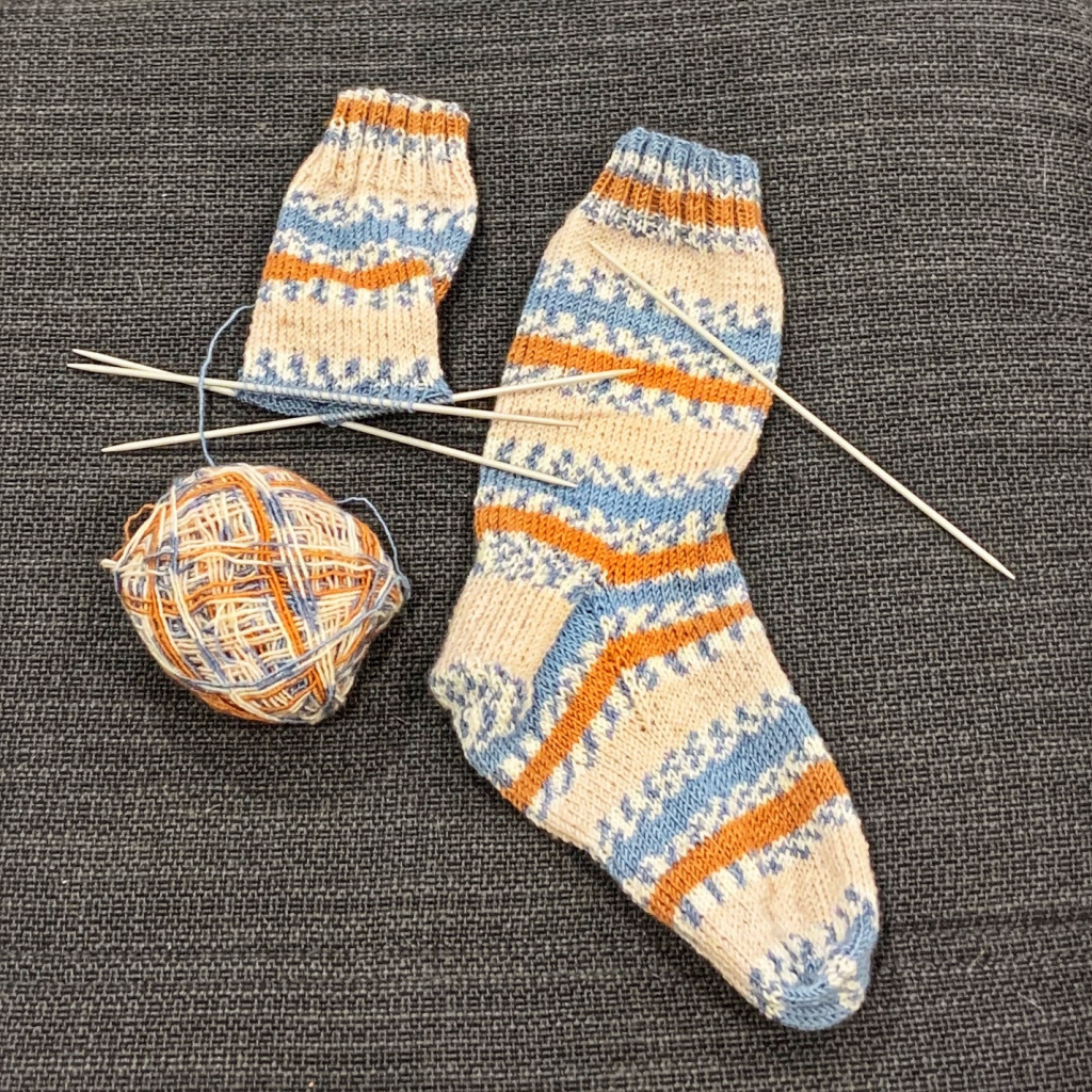 Flat lay of one finished sock and the second started