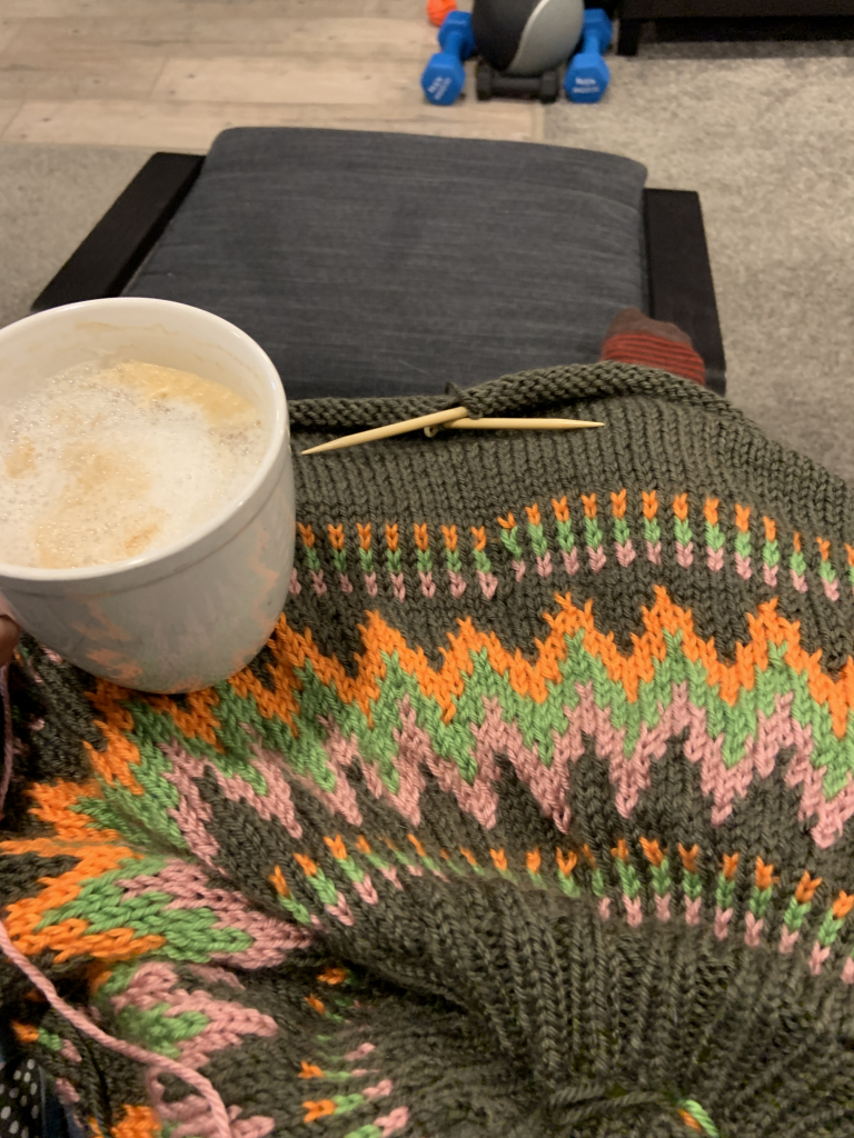 Close up of finished yoke of sweater with a tea in hand