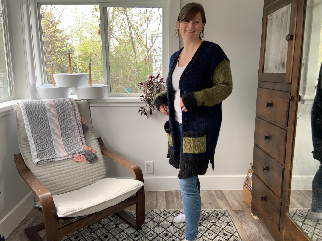 female wearing handknit black, navy and olive cardigan