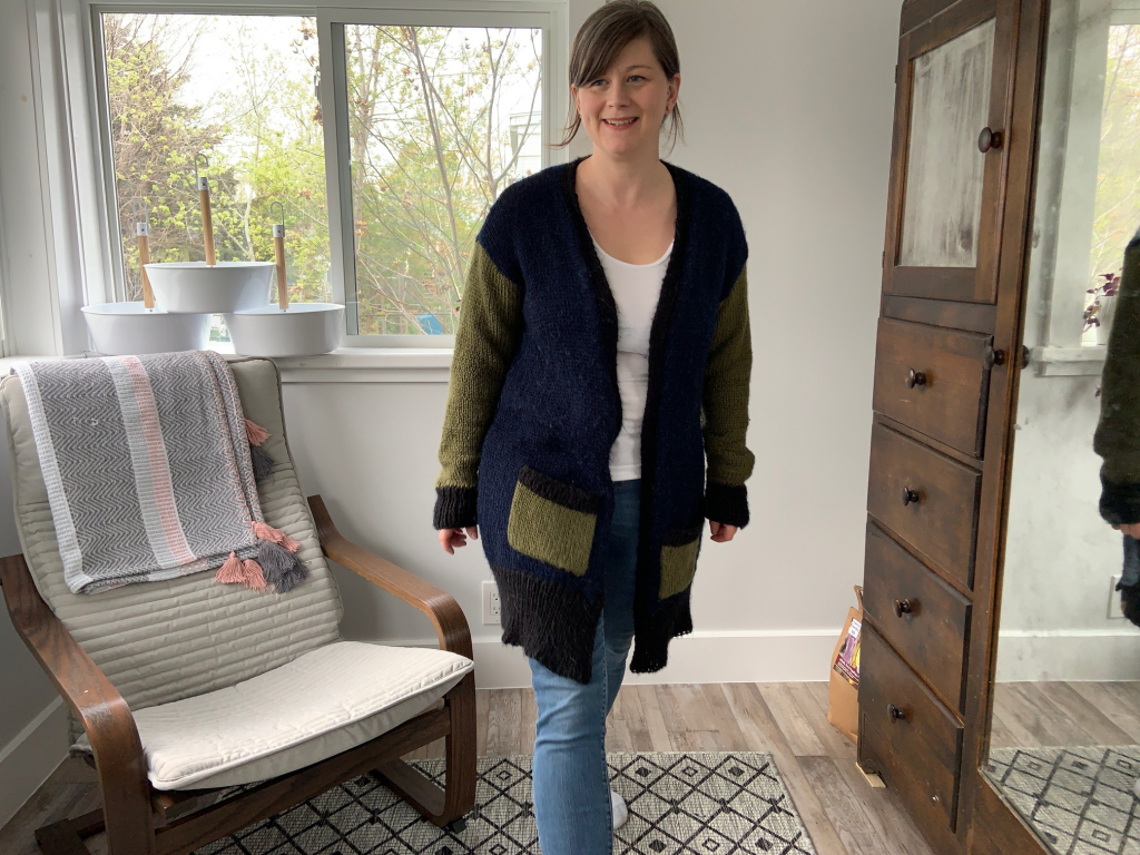 female wearing handknit black, navy and olive cardigan in a different post