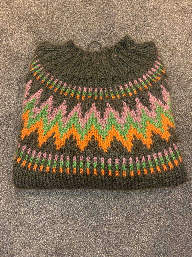multicoloured sweater folded and sitting on the floor