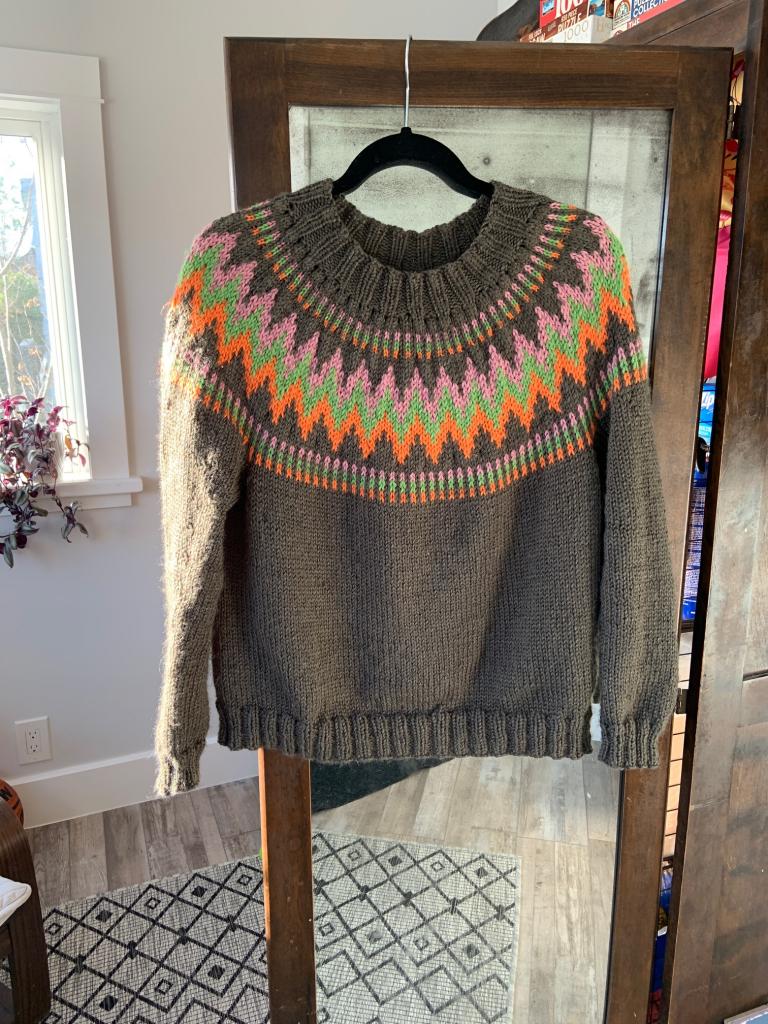 handknit sweater hanging on door of vintage armoire