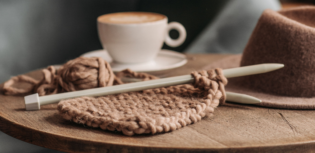 Image of knitting project in progress in brown roving wool on a table with a felt hat and cup of coffee in the background.