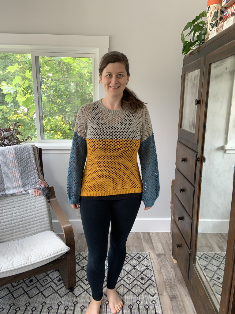 Image of maker wearing finished colour blocked crochet pullover in teal, grey and ochre.