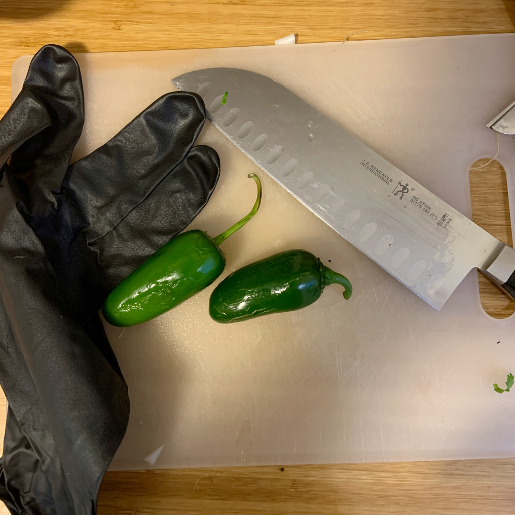 Jalapeno peppers, a knife and nitrile glove on a cutting board